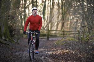 Mann, der Mountainbike durch Wälder reitet foto