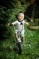 kleiner fröhlicher Junge auf dem Fahrrad foto