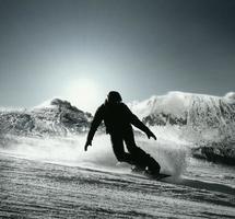 Die Snowboarder-Silhouette geht an der Hochgebirgsskipiste hinunter foto
