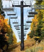 leere Skiliftstühle und Herbstlaub