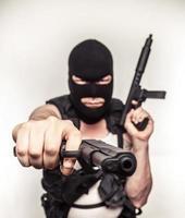 Farbterrorist mit Waffen Skimaske mit großen Augen ernst