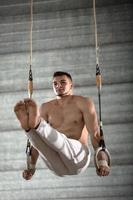 Sportler oben ohne macht eine schwierige Übung auf Gymnastikringen in