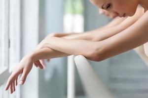 die Hände zweier klassischer Balletttänzer in der Barre