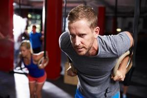Mann im Fitnessstudio, das mit Turnringen trainiert foto
