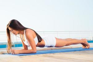 Frau, die auf Yogamatte trainiert foto