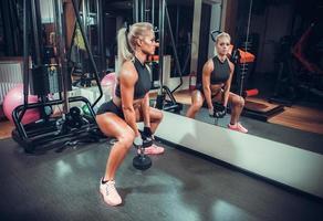 schöne Frau, die mit einer Hanteln in einem Fitnessstudio trainiert foto