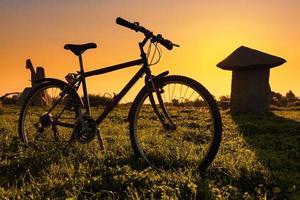 Fahrrad auf der Wiese bei Sonnenuntergang foto