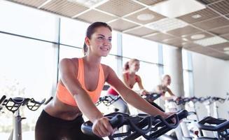 Gruppe von glücklichen Frauen, die auf Heimtrainern im Fitnessstudio reiten foto