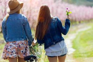 zwei junge Frauen mit einem Oldtimer auf dem Feld. foto