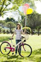kleines Mädchen mit Fahrrad und Luftballons foto