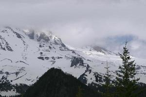 Wolken heben sich über schneebedeckten Berg
