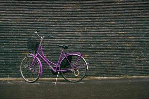 klassisches Vintage lila Hipster Fahrrad auf der Straße foto