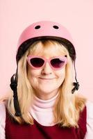lustige Frau, die reale Leute des Fahrradhelmporträts rosa Hintergrund trägt