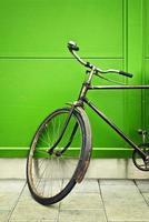 altes Fahrrad, das auf grüne Wand stützt foto