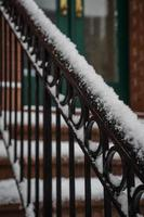 schneebedecktes Eisengeländer des braunen Steins mit Türen im Hintergrund
