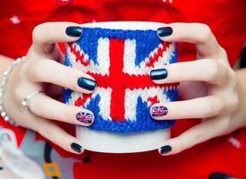 Frauenhände halten die Tasse mit britischem Symbol