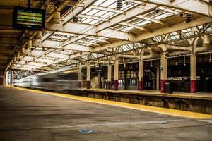 schnell fahrender Zug an einem Bahnhof