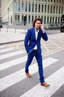 hübscher Geschäftsmann in einem Anzug, der auf seinem Smartphone spricht foto