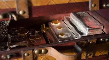 Truhe aus Gold + Silbermünzen und Barren foto