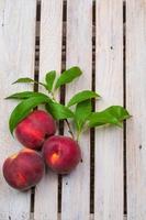 Pfirsiche auf hölzernem Hintergrund foto