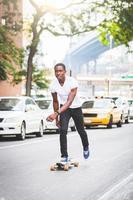 schwarzer Junge, der mit Longboard auf der Straße skatet