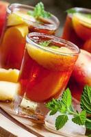 Eis Pfirsich Tee mit Stücken von Obst, Eis und Minze foto