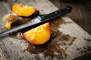 Scheibe saftiger Pfirsich auf Brett und Messer foto