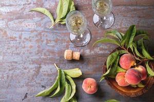 Pfirsiche auf Zweig mit Champagner foto