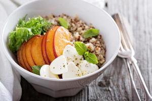 Quinoa-Schüssel mit Pfirsich und Mozarella foto