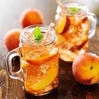 Glas Pfirsich-Tee mit gestreiftem Stroh foto