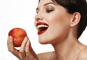 schneeweißes Lächeln und Pfirsich in der Hand foto