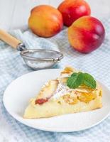 Scheibe Pfirsich-Clafoutis auf einem weißen Teller foto