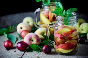 Glas köstliches erfrischendes Getränk aus Pfirsichfrüchten und Pflaumen foto