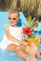 kleines Mädchen mit Cocktail im Strandurlaub. foto