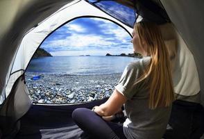 glückliche Frau, die in einem Zelt sitzt foto