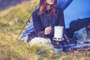 eine Frau, die mit tragbarem Gasherd beim Zelten kocht