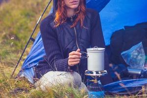Frau Camping und Kochen mit tragbaren Herd foto