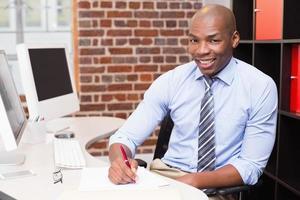 Porträt des Geschäftsmannes, der Dokument am Schreibtisch schreibt foto