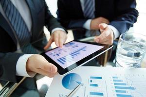 Zwei Geschäftsleute diskutieren Dokumente auf einem Tablet foto
