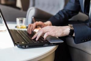 Geschäftsmann, der mit Dokumenten und Laptop arbeitet foto