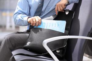 Geschäftsmann, der auf einem Stuhl sitzt und Dokumente herausholt foto