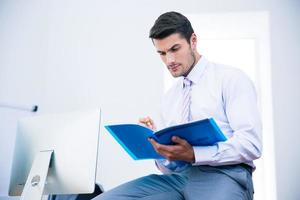 Geschäftsmann sitzt auf dem Tisch und liest Dokument foto
