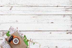 leerer weißer Holztisch mit Werkzeugen für Abenteuer und Reisen foto
