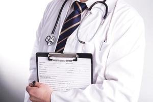 männlicher Arzt bereit, Patienteninformationen zu schreiben foto
