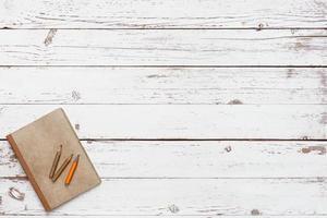 weißer leerer Holztisch mit handwerklichem Grunge-Notizbuch foto