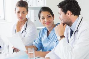 Ärzte und Krankenschwester diskutieren über Dokument foto