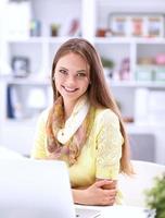 Frau mit Dokumenten, die auf dem Schreibtisch sitzen foto
