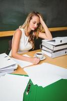schöne Geschäftsfrau, die Dokument am Schreibtisch schreibt foto