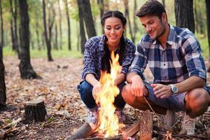 Paar und Lagerfeuer im Wald foto