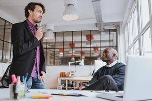 zwei junge Büroangestellte diskutieren über die Arbeit im Büro foto